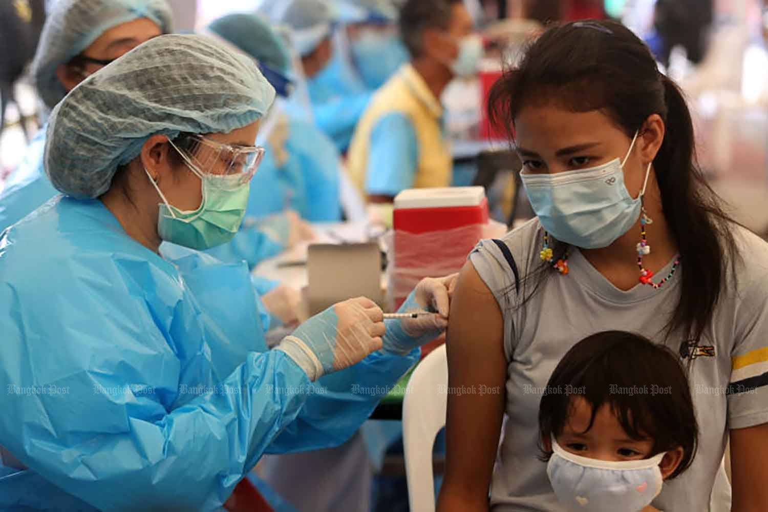 A woman is given a Covid-19 jab at Lotus Rama IV where an area has been converted into a vaccination venue for people in communities in Klong Toey in the capital where the virus has been spreading rapidly in recent days. (Photo by Wichan Charoenkiatpakul)