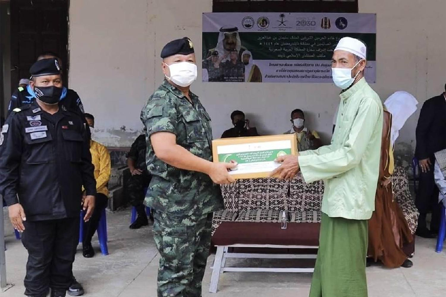 Fourth Army commander Lt Gen Kriangkrai Sirak hands over a gift box from King Salman bin Abdulaziz Al Saud of Saudi Arabia to a Pattani resident. Food boxes were given away to locals to help them break their fast at dusk during Ramadan. (Photo by Fourth Army)