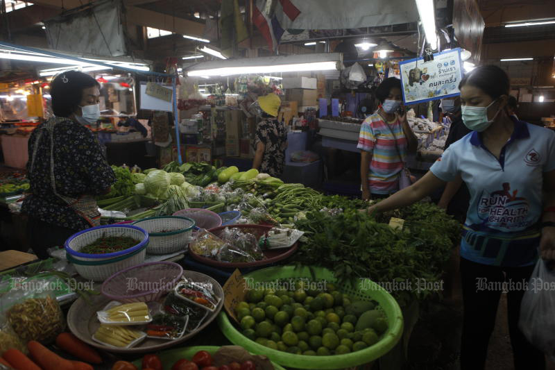 A vendor waits for a customer to select vegetables at Pak Kret market in Pak Kret district in Nonthaburi on April 24, 2021. (Photo by Nutthawat Wicheanbut)