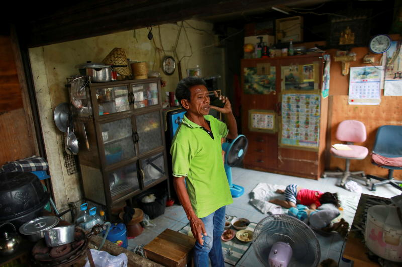 A man and a child are seen in a house in the Klong Toey slum in Bangkok on Tuesday. (Reuters photo)