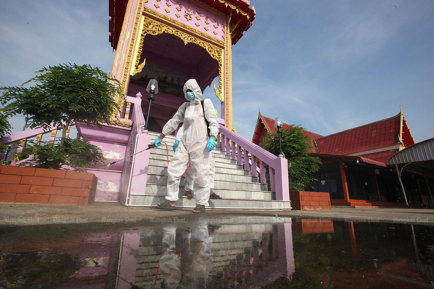 Clean send-off: Monks in protective overalls spray disinfectant around the crematorium at Wat Bang Muang in Nonthaburi's Bang Yai district, one of the temples equipped to cremate the bodies of those who died of Covid-19. (Photo by Pattarapong Chatpattarasill)