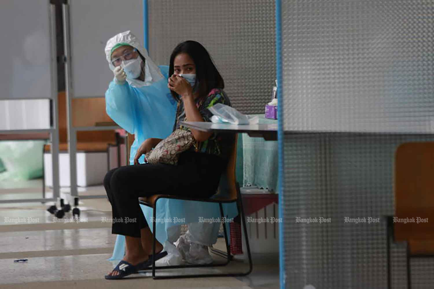 A disease control worker advises a social security fund member about the process of free Covid-19 testing in Bangkok on Wednesday. (Photo: Arnun Chonmahatrakool)