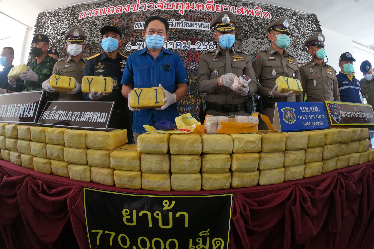 Nakhon Phanom governor Kraisorn Kongchalard, centre, and senior police and soldiers announce the arrest of the four people and seizure of 770,000 meth pills in Tha Uthen district of Nakhon Phanom, at a media briefing on Thursday. (Photo: Pattanapong Sripiachai)