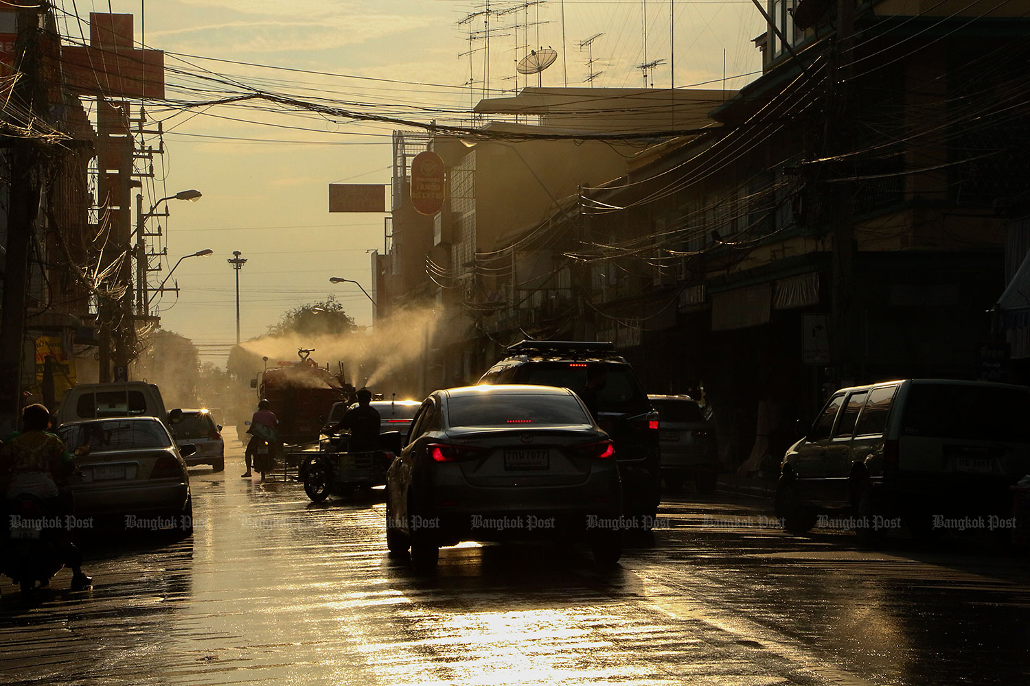A truck sprays disinfectant on to the streets in Ratchaburi's Muang district on Thursday after a spike in Covid-19 cases. Several of those infected were found to have taken part in social activities. (Photo by Saichon Srinuanjan)
