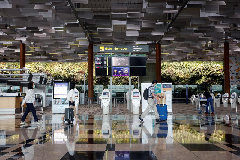 FILE PHOTO: People wearing protective face masks walk past self check-in machines, amid the spread of the coronavirus disease (Covid-19) at Changi Airport in Singapore Oct 12, 2020. (Reuters)