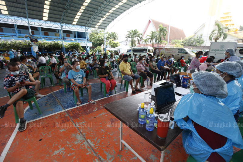 Local residents register for Covid-19 jabs in Klong Toey district of Bangkok on Wednesday. (Photo by Varuth Hirunyatheb)
