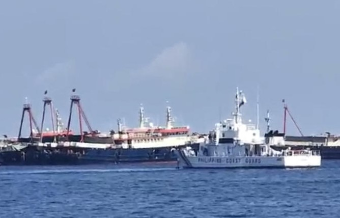 This handout video grab taken on April 27, 2021 and received from the Philippine Coastguard on May 5, 2021 shows the Philippine coastguard ship BRP Cabra (front) monitoring Chinese vessels at Sabina Shoal, a South China Sea outcrop claimed by Manila located about 135 kilometres (73 nautical miles) west of the Philippine island of Palawan. (Philippine Coastguard / AFP)