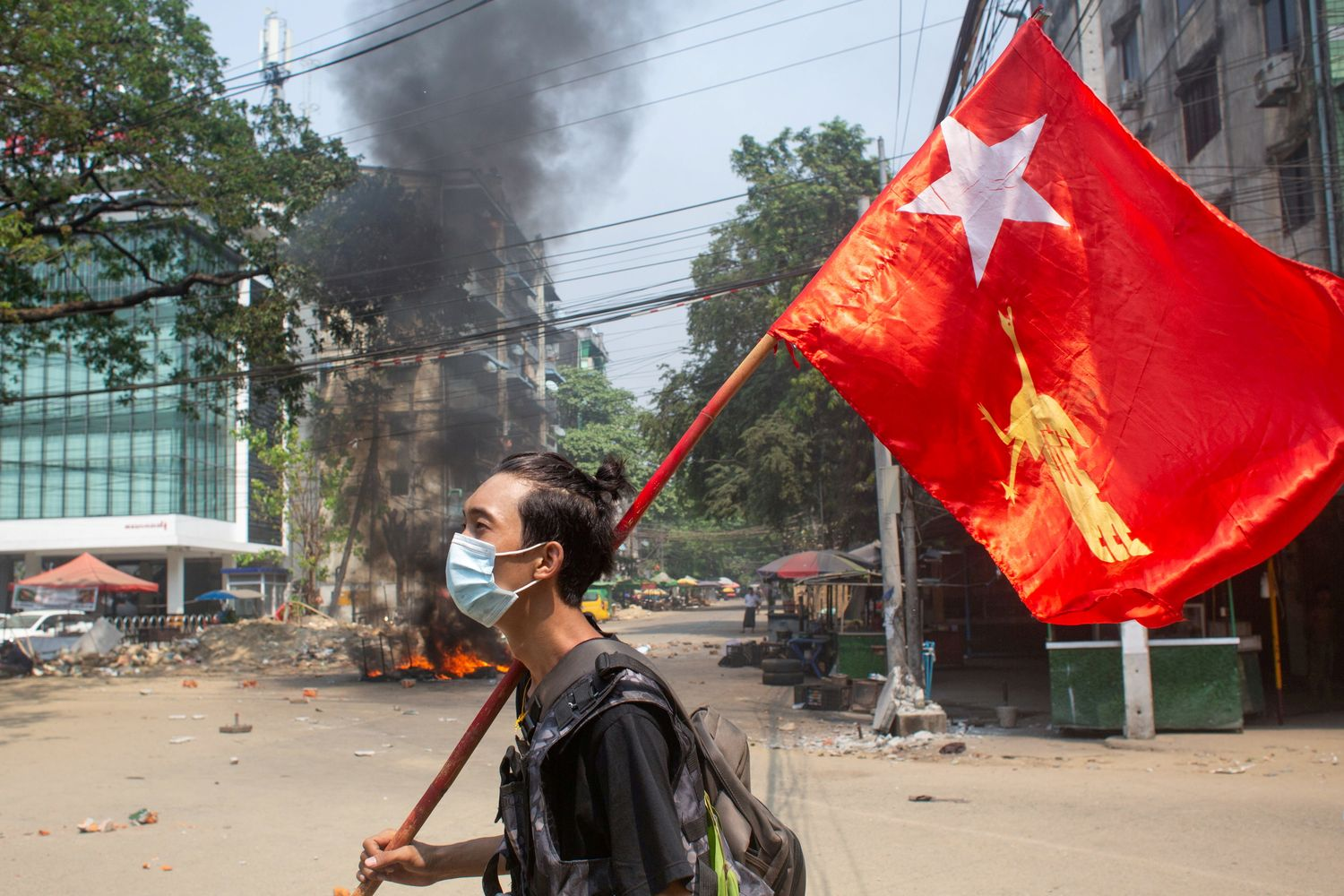 A man holds a National League for Democracy flag during a protest against the military coup, in Yangon on March 27. (Reuters photo)