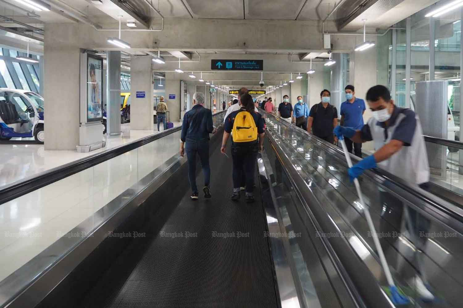A cleaner keeps the moving walkway hygienic for travellers at Suvarnabhumi airport. (Photo by Dusida Worrachaddejchai)