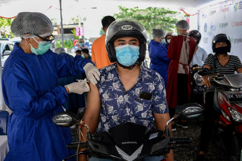 FILE PHOTO: A man receives a shot of Covid-19 coronavirus vaccine at a drive-through vaccination service in Kuta on Indonesia's resort island of Bali on April 21, 2021. (AFP photo)