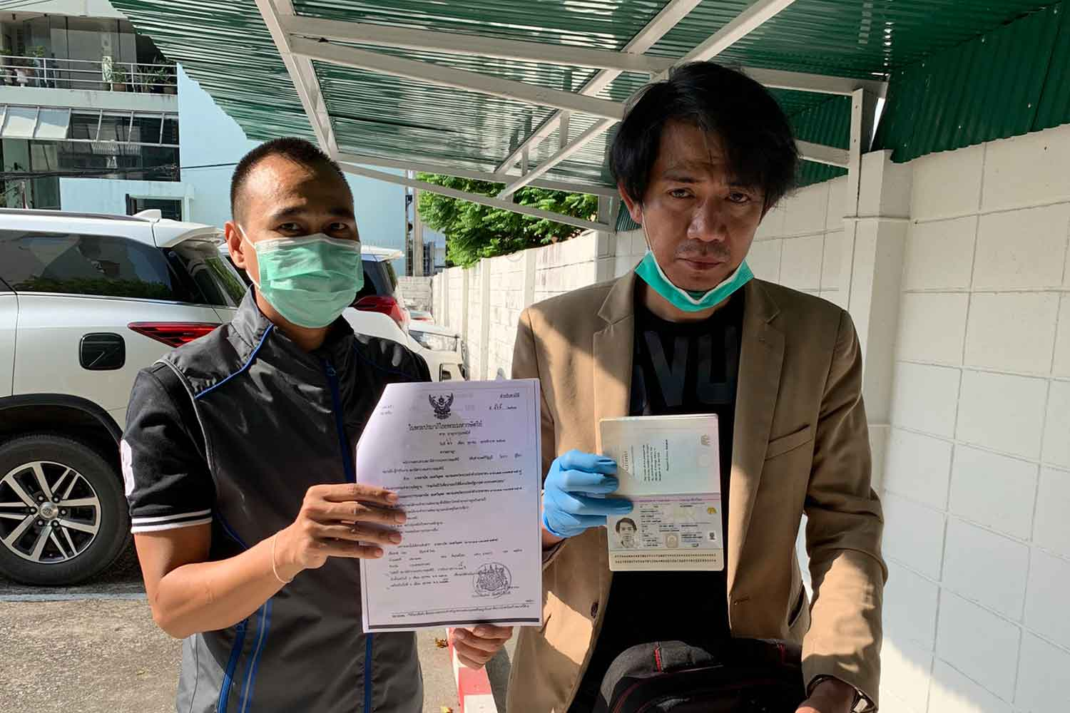Thanat Amatawimut, 42, right, is arrested in a commercial bank parking lot in Bangkok on Monday, accused of exchanging forged US banknotes with a face value of $39,000. (Photo supplied)