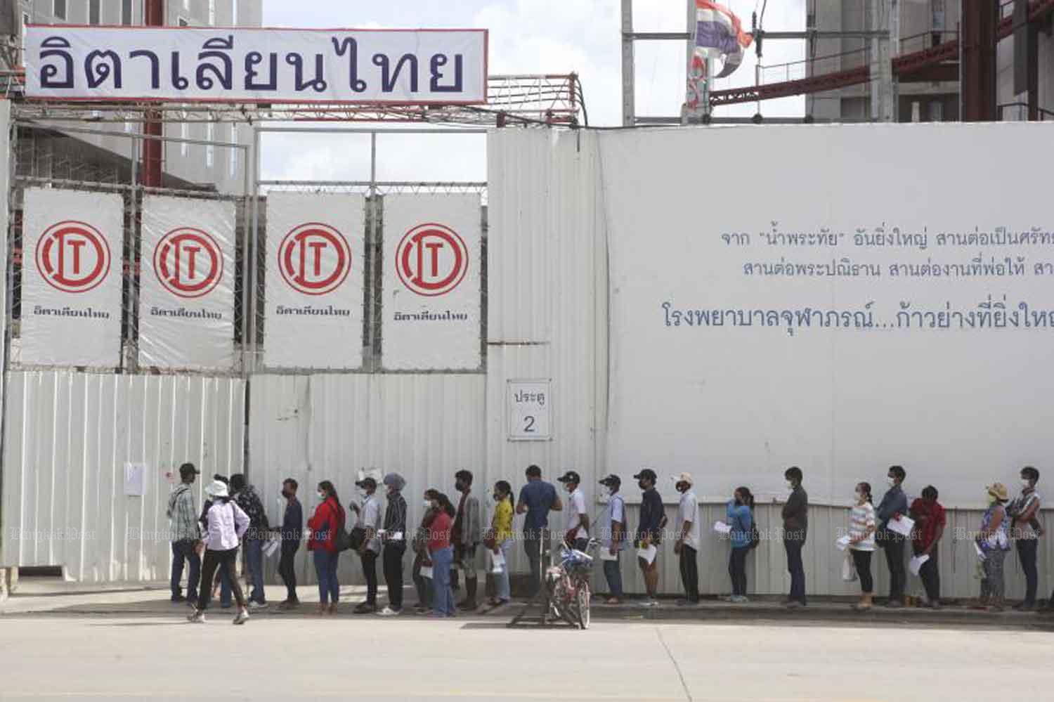 People living near the construction workers' camp of Italian-Thai Development Plc in Laksi district, Bangkok, line up for Covid-19 tests on Tuesday. The camp is one of 21 active clusters in 16 districts of Bangkok (Photo: Pattarapong Chatpattarasill)