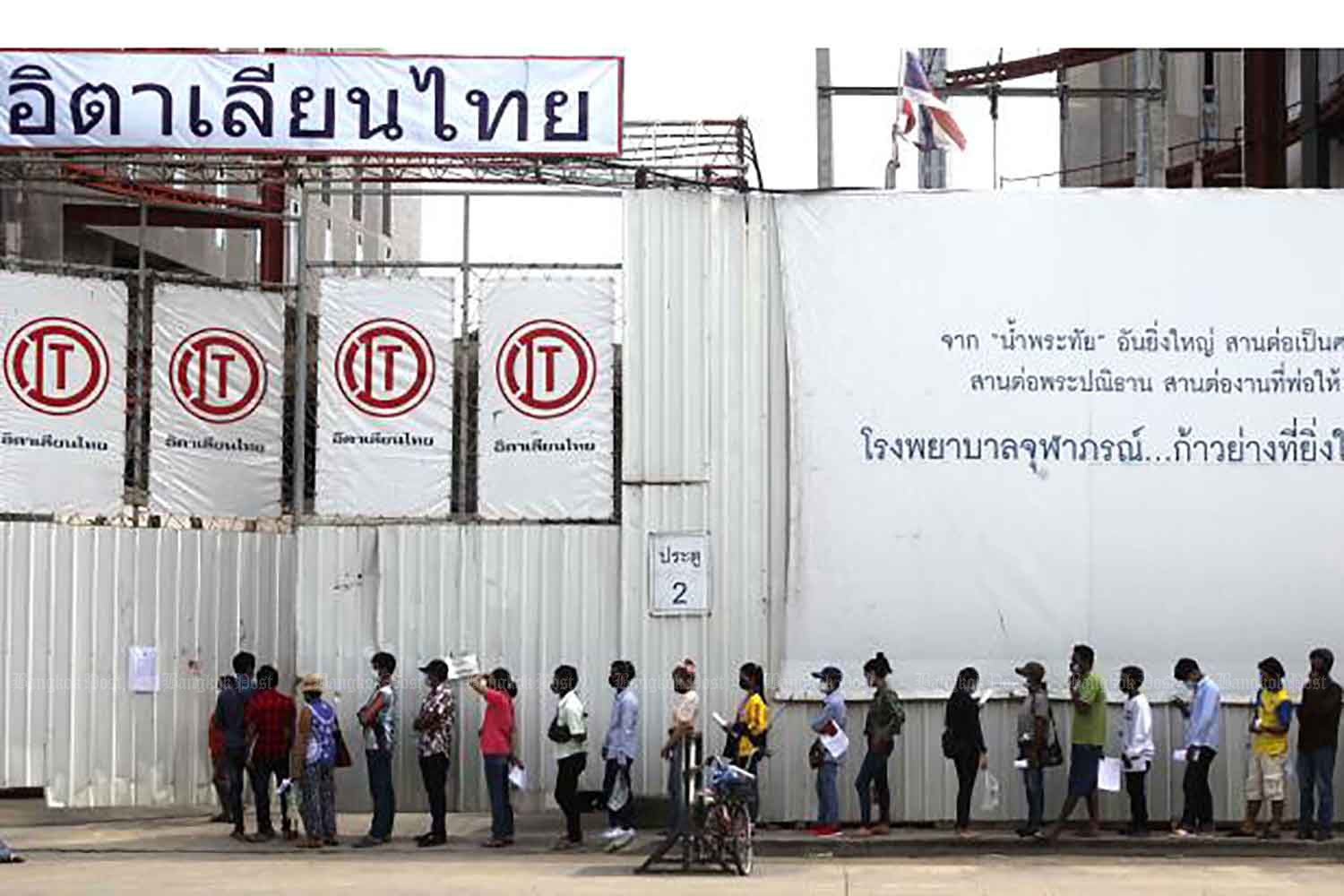 Workers form a long line as they wait to undergo a Covid-19 test at their construction site in Bangkok's Laksi district on Tuesday. Residents in communities around the site are also being tested. So far, 680 of the 1,667 workers have tested positive. Of them, 120 are being treated in hospital. (Photo: Pattarapong Chatpattarasill)