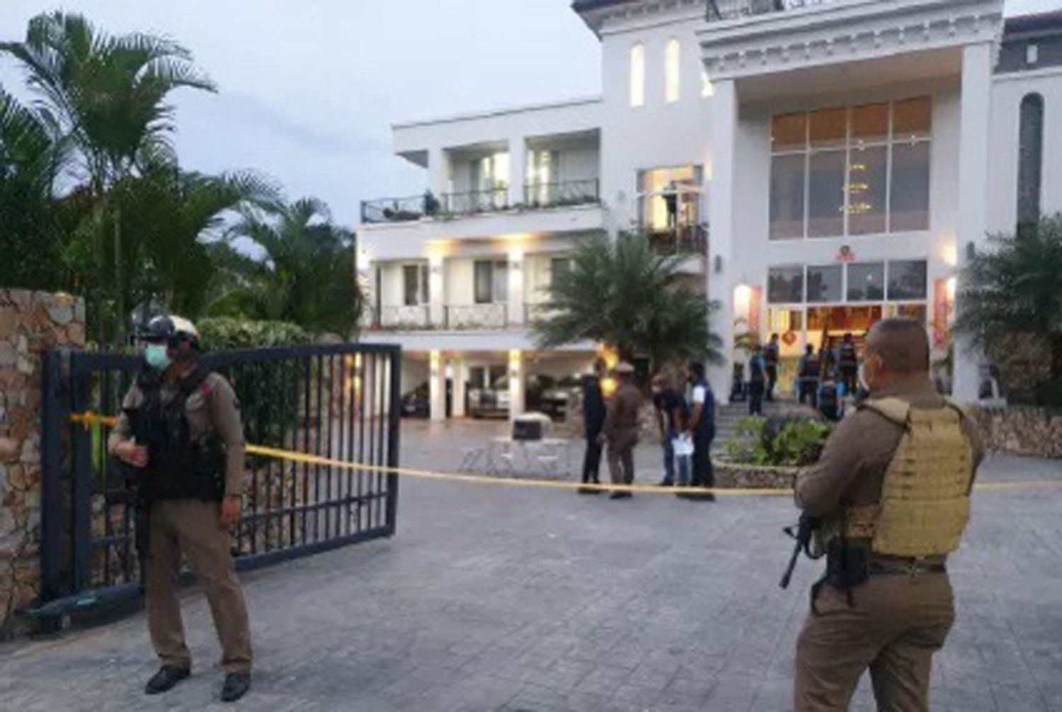 Police guard the luxury house at a golf course in Bang Lamung district, Chon Buri, where two officers were shot on Wednesday while executing an arrest warrant. A Chinese man was later arrested. (Photo supplied/ Wassayos Ngamkham)