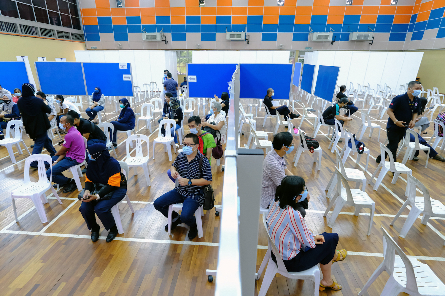 People wait in an observation area after receiving a dose of the Sinovec Covid-19 vaccine at the Pandamaran Sports Hall in Port Klang, Selangor, Malaysia, on Thursday. (Bloomberg Photo)