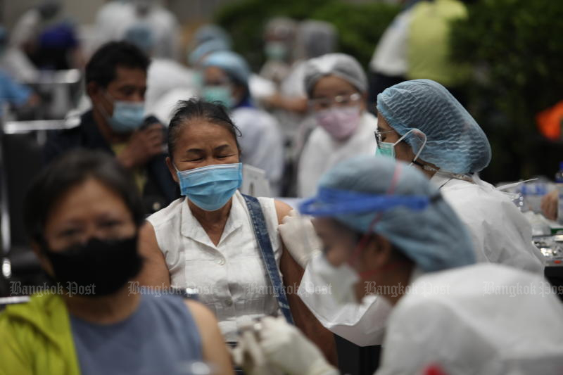 A woman receives a Covid jab at Siam Paragon, a vaccination site run by Bangkok Hospital, on Friday. The service was provided for people who registered though Mor Prom app.(Photo: Apichart Jinakul)