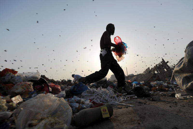 Insects fly around labourers sorting and collecting rubbish for recycling at a dump in Hefei, Anhui province, China, on May 18, 2011. (Reuters photo)