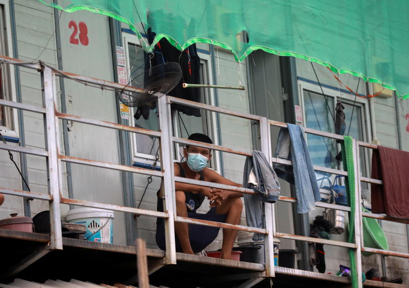 A Myanmar migrant worker sits outside his room on Saturday, where he has been stuck for 12 days due to lockdown measures after more than a thousand Covid-19 cases were detected in workers' dormitories in Bangkok.