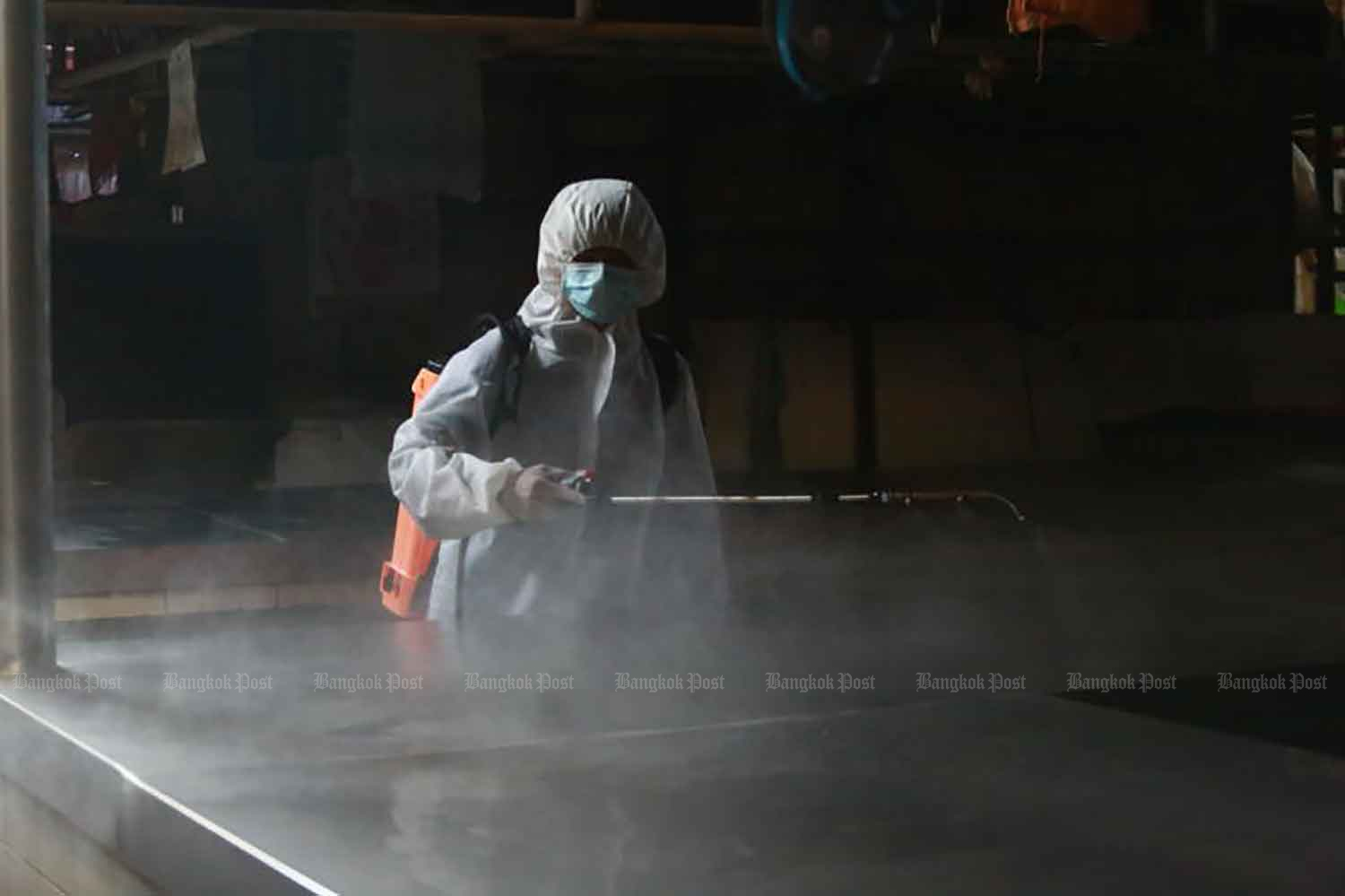 A disease control worker sprays disinfectant to prevent a Covid-19 outbreak at a wholesale market in Muang district of Samut Prakan on Monday. (Photo: Somchai Poomlard)