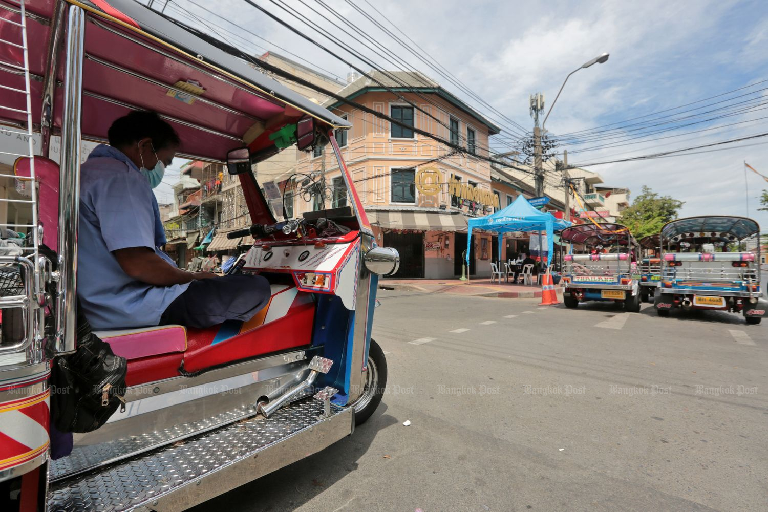 A tuktuk driver waits for customers near Pak Klong Talat fresh flower market in Bangkok on Tuesday, the second day the market was closed by a City Hall order in the wake of Covid-19. (Photo by Chanat Katanyu)