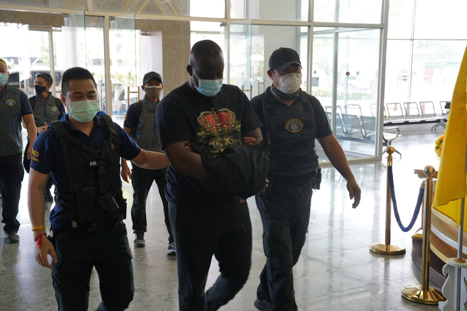 Nigerian Ezeneche Uzochukwu Jorome (centre), an alleged leader of a romance scam, is taken into custody by Crime Suppression Division police on Monday. (Crime Suppression Division photo)