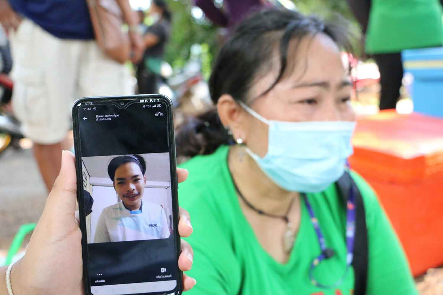 Udomsri Kachonklin, 40, cries near the Nan River in Muang district of Phichit on Tuesday as a person shows the picture of her son who went missing after jumping into the water to protest 14-day quarantine for returning from Bangkok. (Photo: Sitthipoj Kebui)