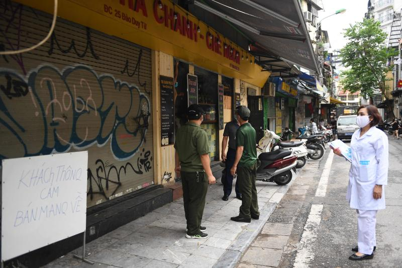 Health and local officials inspect food shops in Hanoi on Tuesday as city authorities expanded closure orders to include restaurant dine-in services, barbershops and hair salons to prevent coronavirus transmission. (AFP photo)