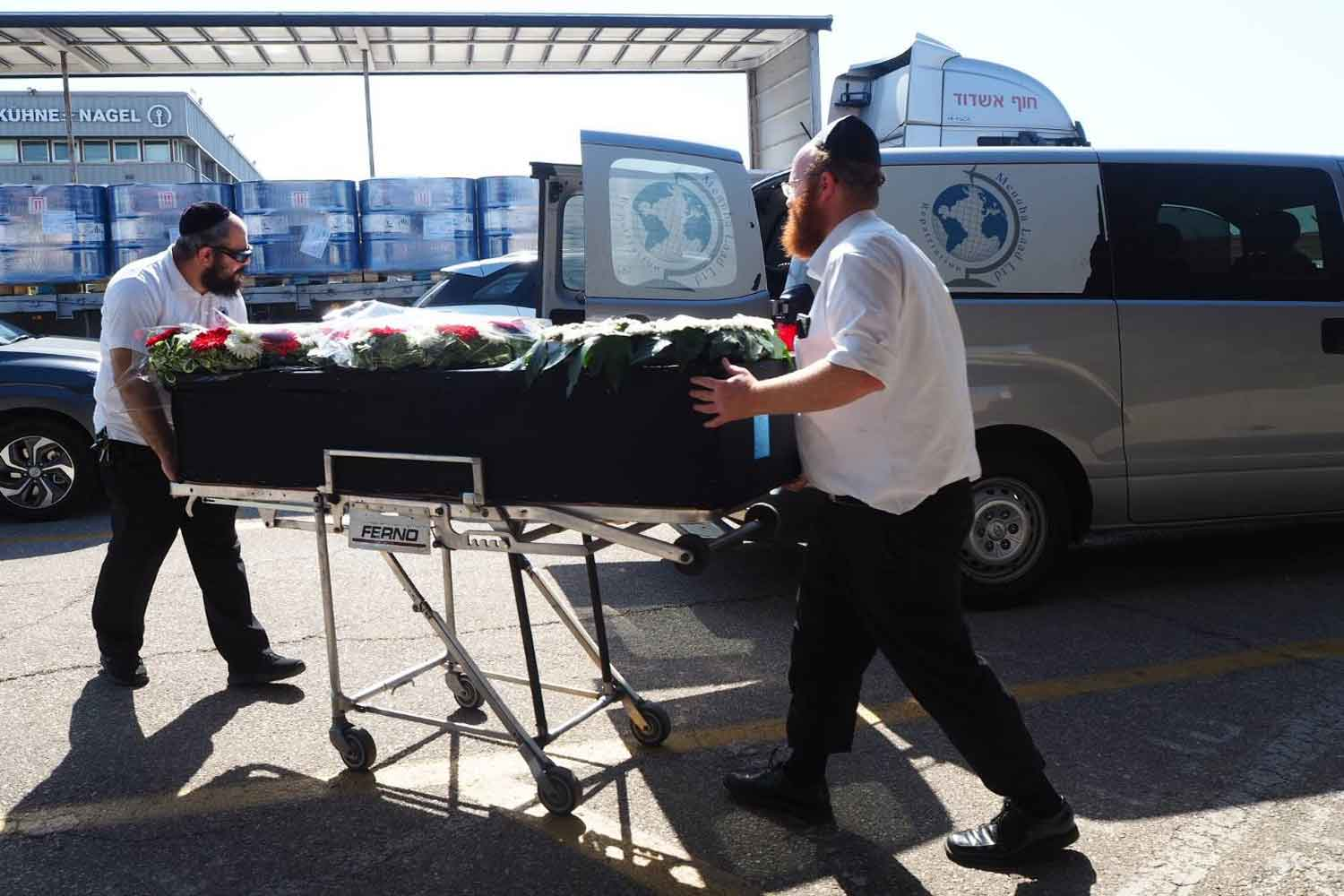 A coffin containing the body of one of the two Thai workers killed in a rocket attack in Israel is moved from a vehicle at Ben Gurion International Airport before being flown to Thailand on Tuesday.  The flight was scheduled to arrive at Suvarnabhumi airport after noon on Wednesday. (Foreign Ministry photo)