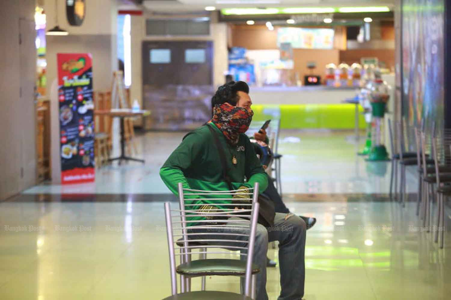 A food delivery man waits for his customer's meal at a shopping centre in Samut Prakan province. (File photo: Somchai Poomlard)