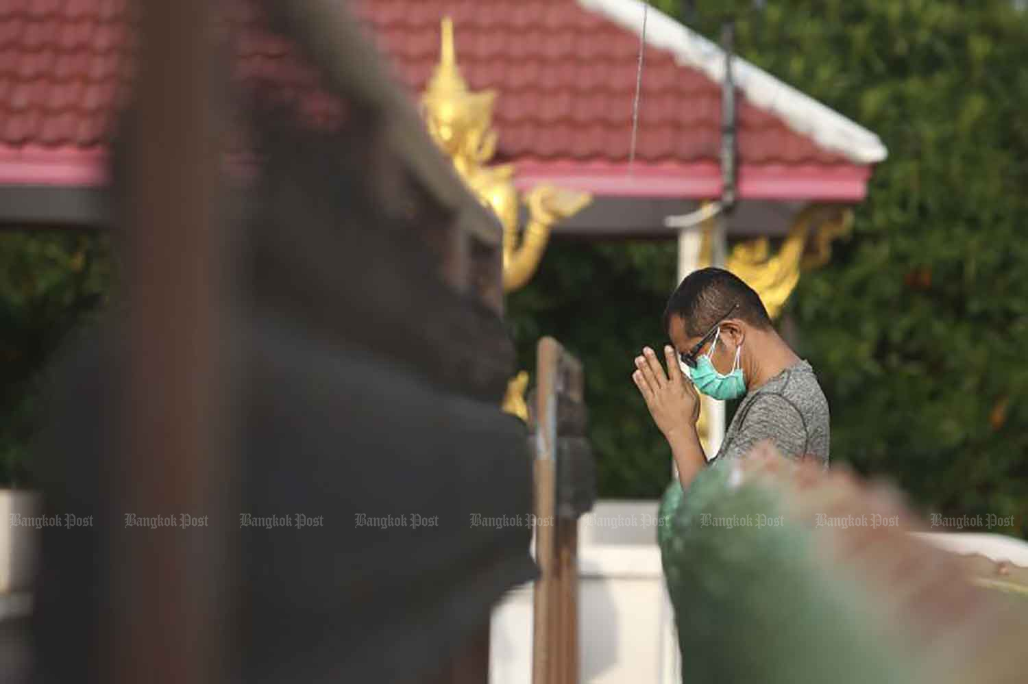 A man wearing a double layer of face masks prays at Wat Bang Chak in Nonthaburi province on Wednesday, when 47 new Covid-19 fatalities and 3,323 new cases were reported. (Photo: Pattarapong Chatpattarasill)