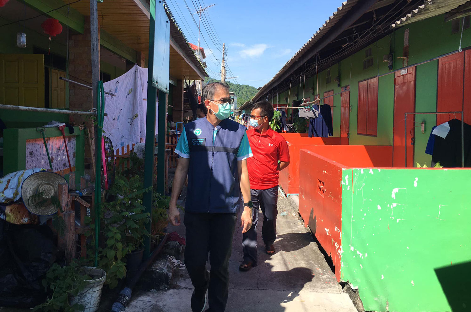 Deputy Chon Buri public health office chief Dr Wichai Thanasophon leads an inspection of living quarters of migrant workers in tambon Bang Sai of Muang district in Chon Buri on Monday. (Photo: Chon Buri public health office)
