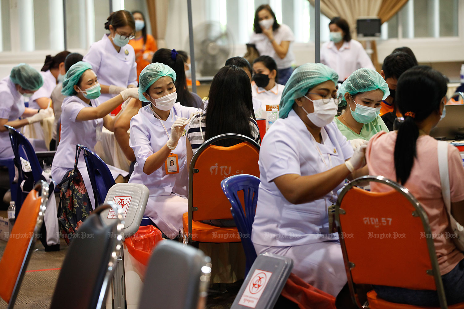 It's rollout time: Medical officials of the Chulabhorn Royal Academy in Laksi district inject at-risk people with Covid-19 vaccines. The academy can provide vaccine doses to between 2,500 and 4,000 people a day. (Photo: Varuth Hirunyatheb)