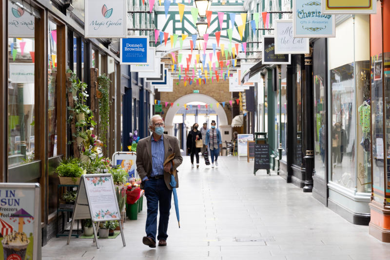 Shoppers walk through an arcade in Bedford, England, on Monday, as the UK plans to reopen to visitors. (Photo: Bloomberg)