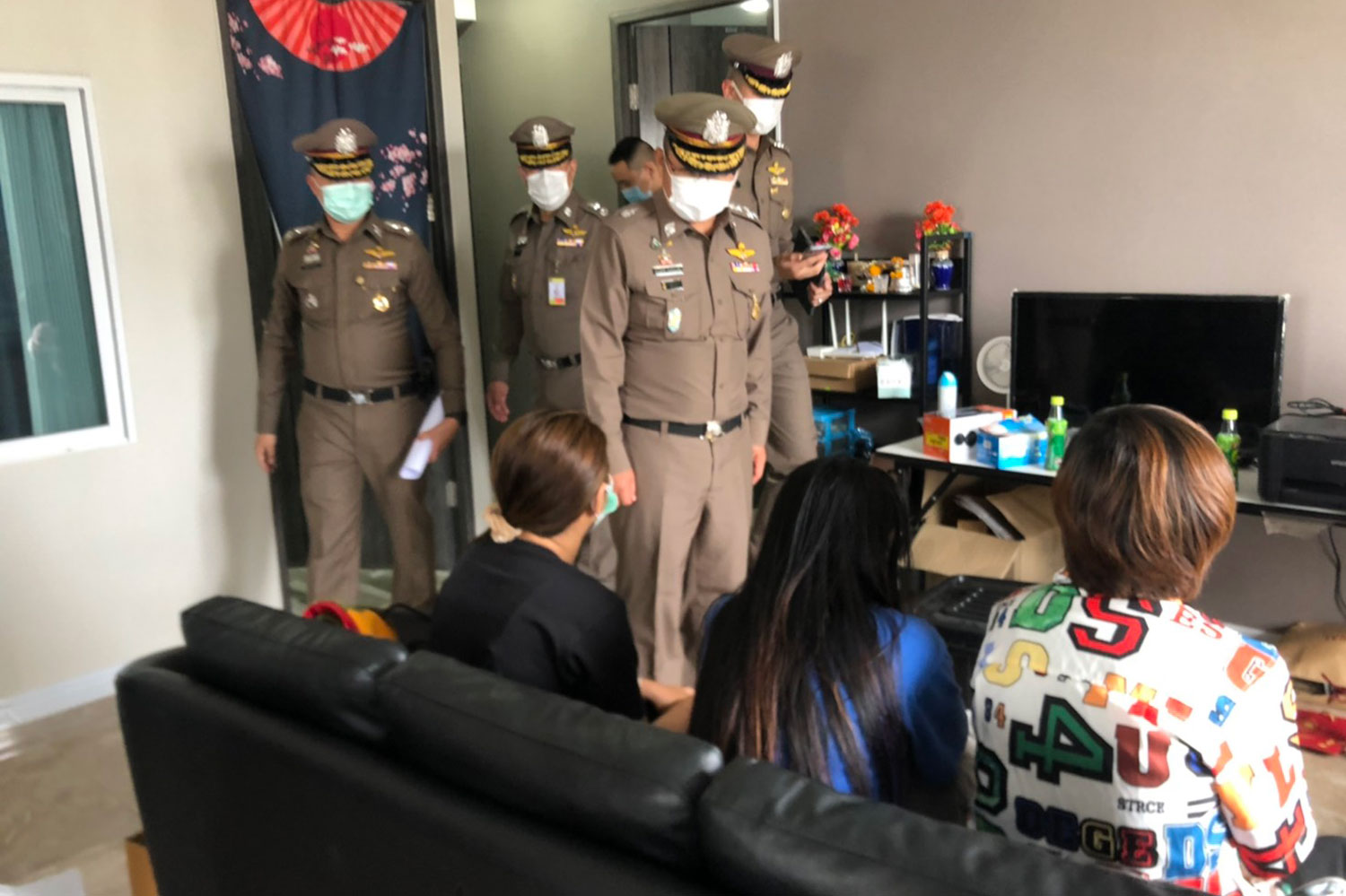 Police confront three of the people caught during the raid on three rooms at a condominium in Bangkok's Bangkok Noi district. They worked for a gambling website with a turnover estimated at more than 100 million baht a month, according to police. (Photo: Wassayos Ngamkham)