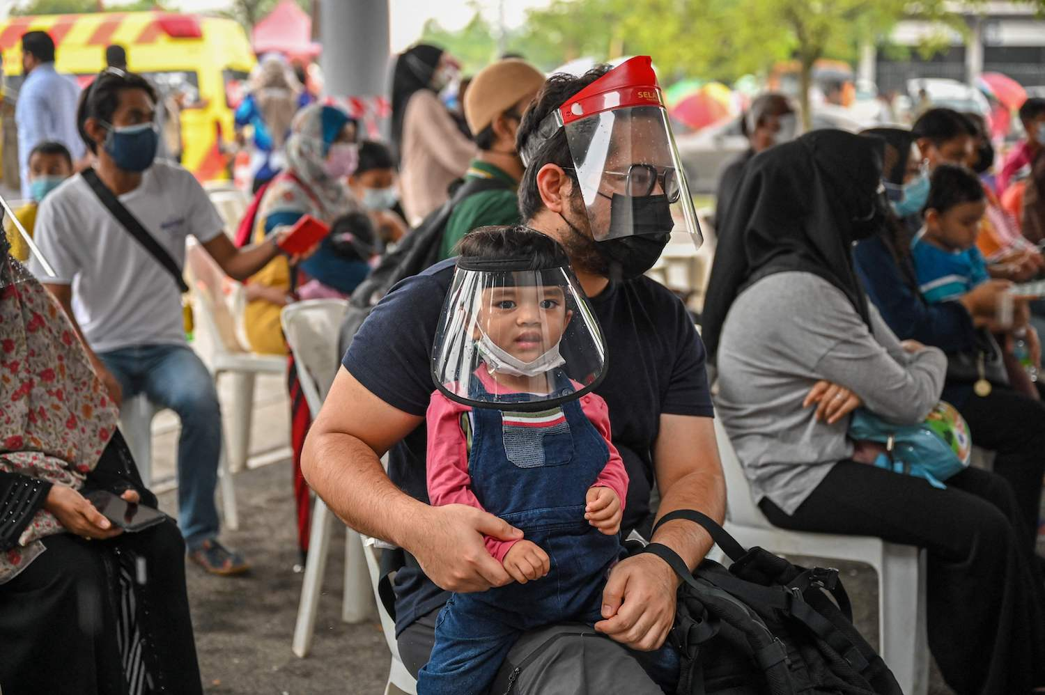 A boy and his father wait for tests at a free coronavirus testing site in Shah Alam, on the outskirts of Kuala Lumpur, on Thursday. (Reuters Photo)
