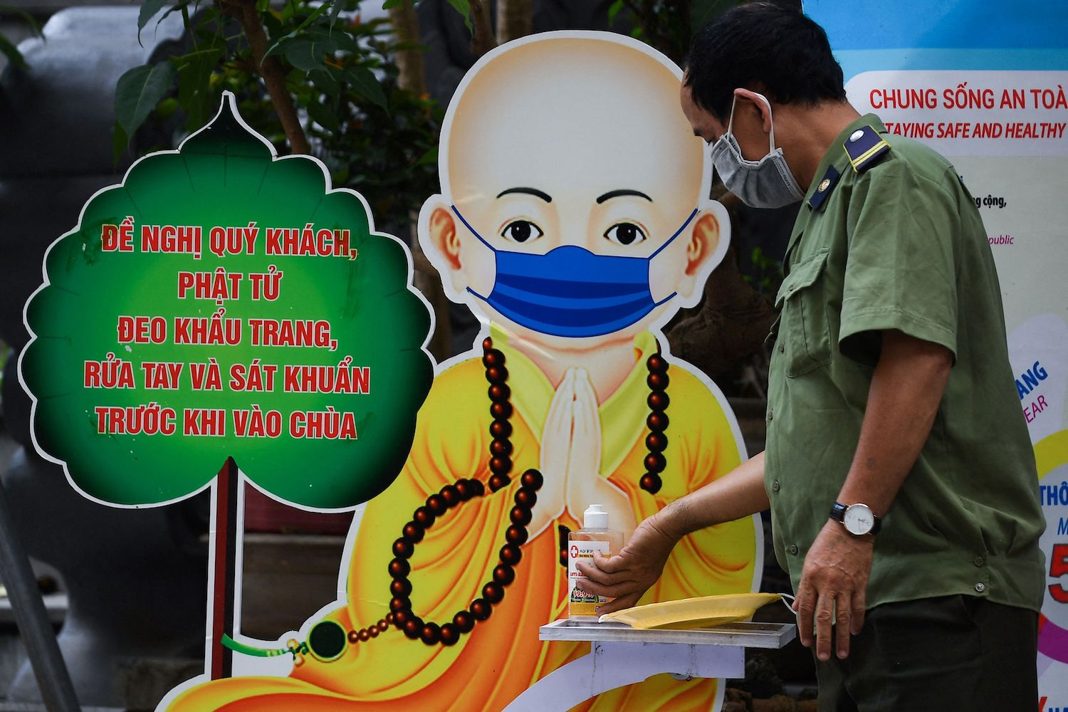 A security officer uses hand sanitiser at the Quan Su pagoda in front of an illustration of a masked monk in Hanoi on Wednesday, when Buddhists across the region celebrated Vesak Day. (AFP Photo)