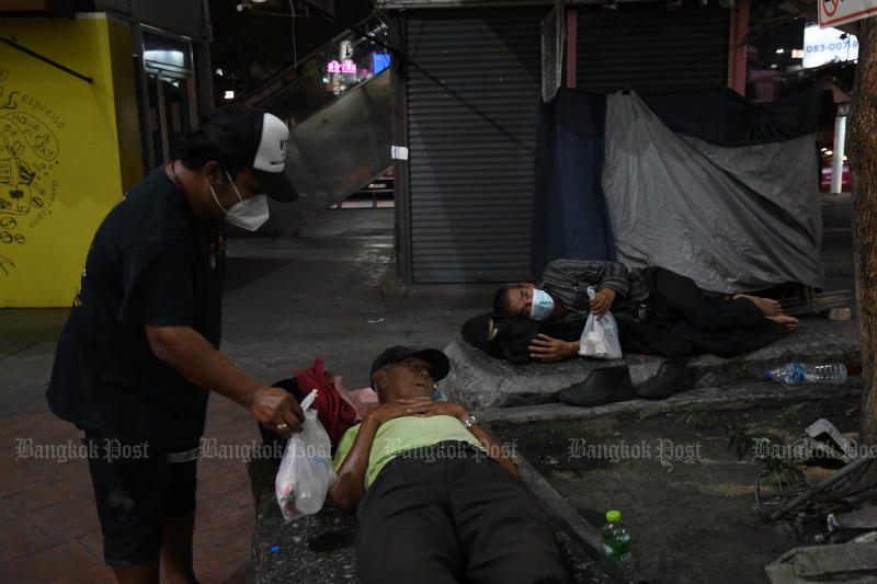 People bring food and masks to homeless people living by Victory Monument on May 1, 2021. (Bangkok Post photo)