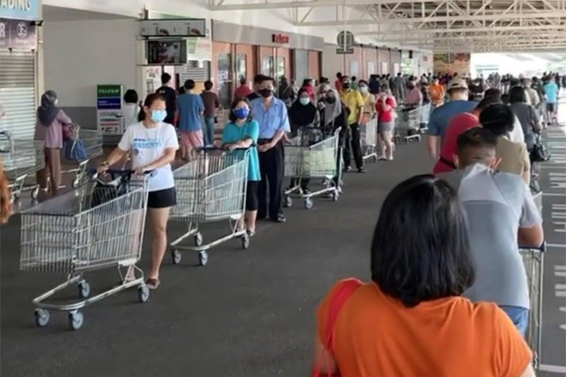 People queue outside a Lotus's supermarket in Gelugor, Penang state, on Friday after a 'total lockdown' was announced in Malaysia. (Reuters photo)