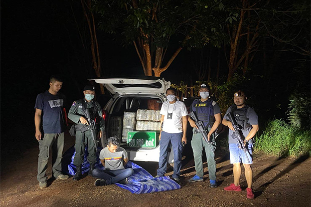 Pranchaiwut Sae Chua (seated) was one of two suspects arrested by border patrol police in That Phanom district of Nakhon Phanom on Saturday, with 400 kilogrammes of dried marijuana in his pickup truck. (Photo by Pattanapong Sripiachai)