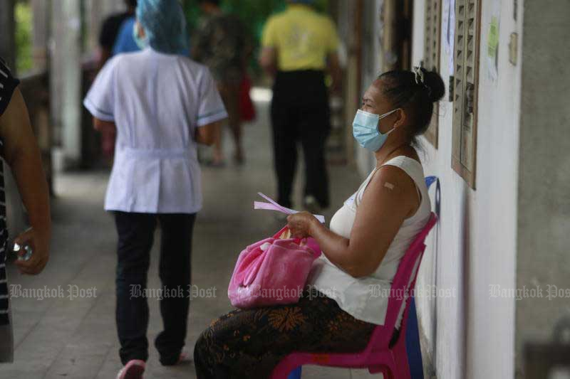A woman sits on a chair during the observation period after receiving a Covid-19 vaccine at an inoculation centre in Muang district of Nonthaburi on Sunday. (Photo: Arnun Chonmahatrakool)