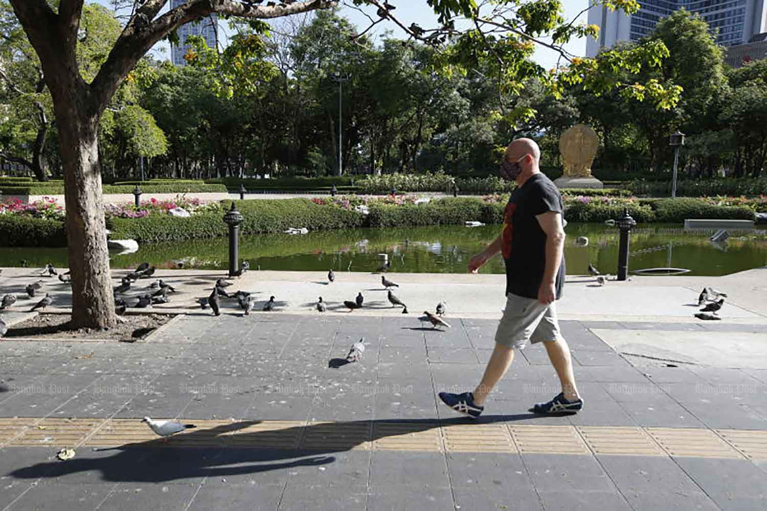 A man walks past the closed Benchasiri Park on Sukhumvit Road in Bangkok on Monday, when the country logged 38 Covid-19 fatalities and 2,230 new cases. (Photo: Wichan Charoenkiatpakul)