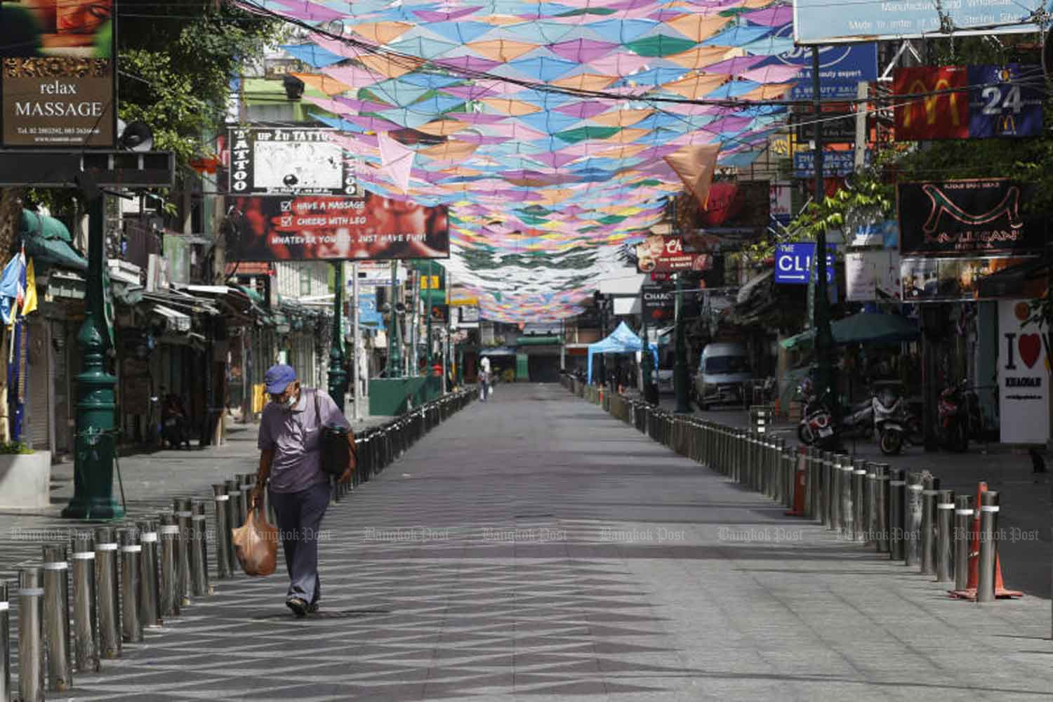 A lone man walks along a deserted street in normally bustling Khao San Bangkok on Sunday. The third wave of Covid-19 has led to strict controls that have brought tourism in the area to a halt. (Photo: Apichit Jinakul)