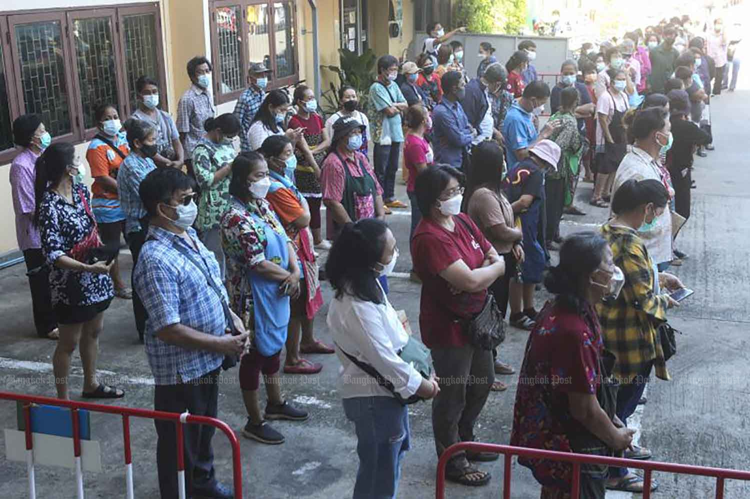 People wait for their Covid-19 test in Pathum Thani province on Tuesday. (Photo: Pattarapong Chatpattarasill)