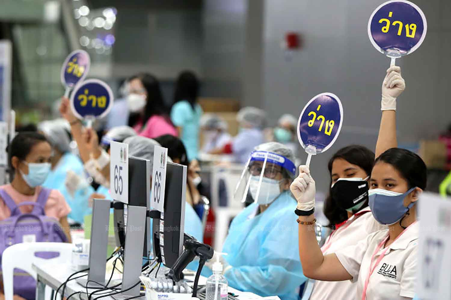 Medical workers raise signs calling forward the next people in line for Covid-19 vaccination, at Bang Sue Grand Station in Bangkok on Tuesday. (Photo: Varuth Hirunyatheb)