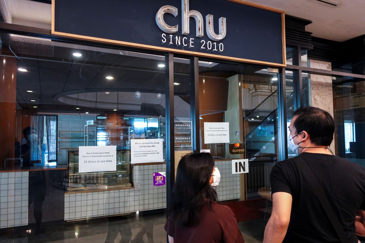 People walk past Chu Chocolate Bar & Cafe, days after it was permanently closed due to the coronavirus disease pandemic in Bangkok on Tuesday. (Reuters photo)
