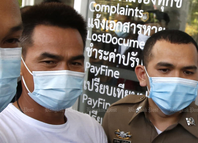 An officer from the Pathumwan police station escorts murder suspect Chaiphol Wipha to the Royal Thai Police airbase for a flight to Mukdahan on Wednesday. (Photo by Wichan Charoenkiatpakul)