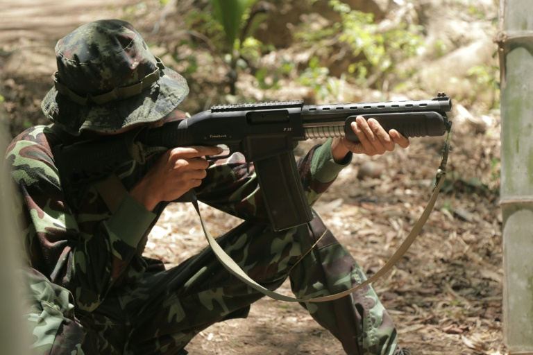 An anti-coup activist in Myanmar aims a weapon while undergoing basic military training at a camp of the Karen National Union.