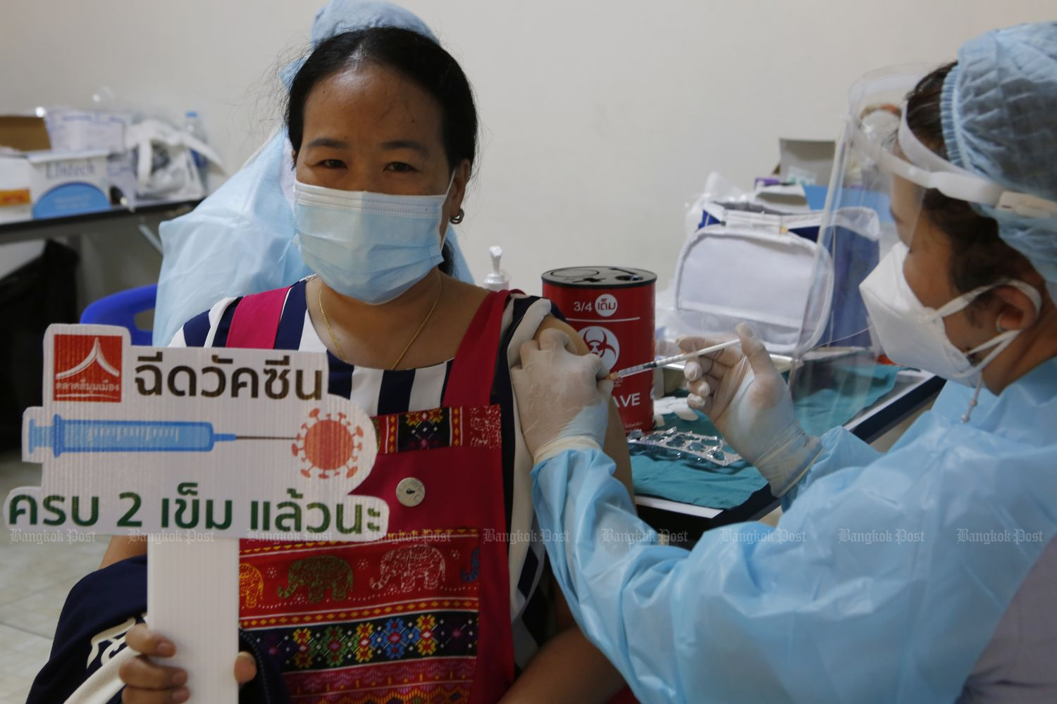 A woman receives her second Covid-19 dose while holding a sign that reads