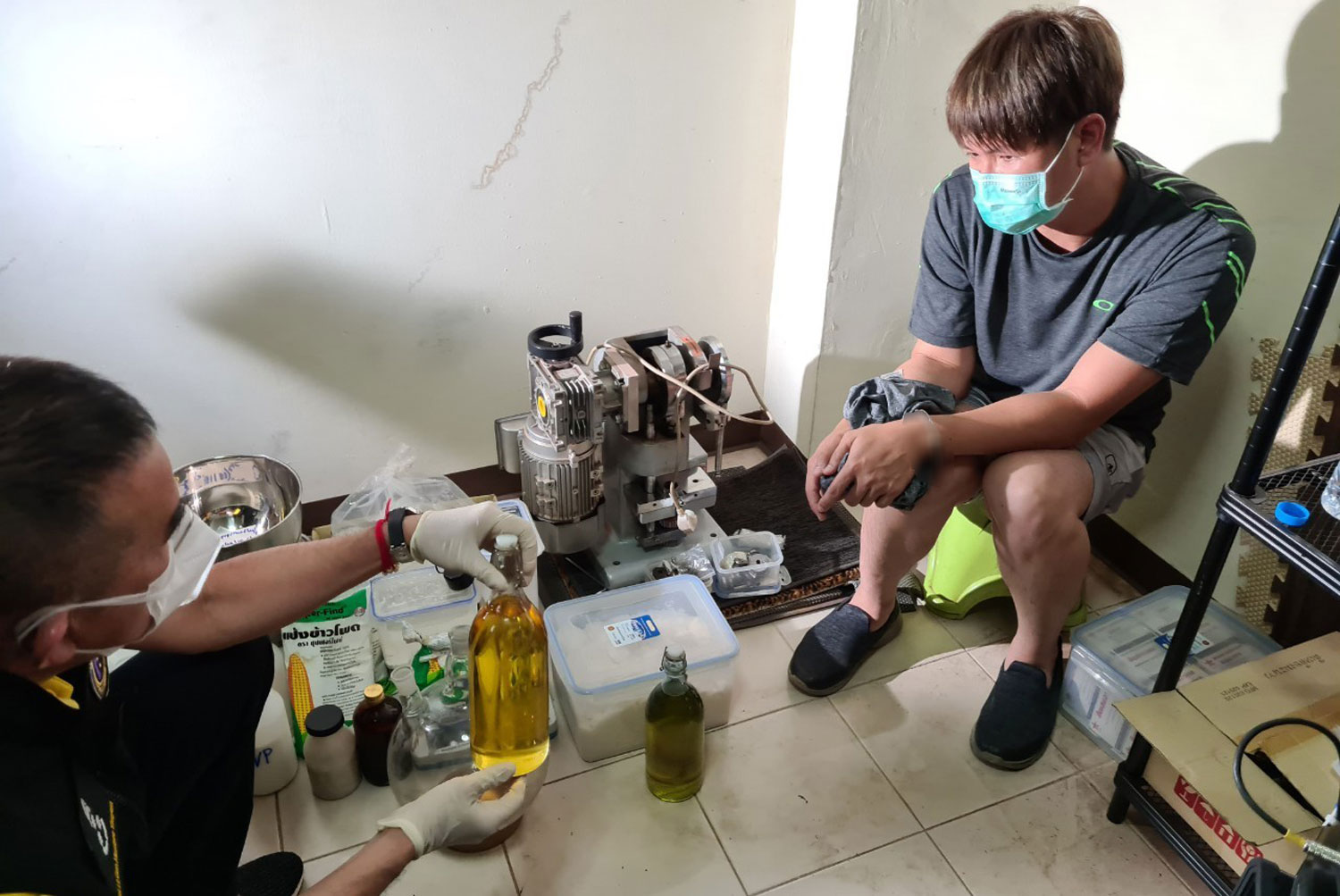 Chemical engineer Pathiwet Suwankhiri (right) is caught during a police raid that netted 20,000 ecstasy pills in Nonthaburi on Saturday. (Police photo)