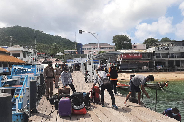 Luggage belonging to Rakeshwar Sachathamakul, his wife Anshoo and their family is moved onto a boat at a pier on Koh Tao in Koh Phangan district of Surat Thani on Sunday. (Photo by Supapong Chaolan)